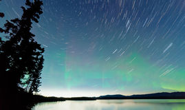 Lake Laberge startrails Aurora borealis display Royalty Free Stock Image