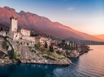 Lake Lago Garda - view of Malcesine village. Old castle on rock Italy. Aerial photo sunset royalty free stock image