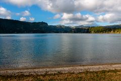 Lake Lagoa das Furnas on Sao Miguel Island, Azores Islands, Port. Ugal. Fresh vegetation lining. Blue sky with intense clouds royalty free stock photography