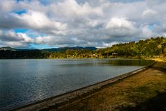 Lake Lagoa das Furnas on Sao Miguel Island, Azores Islands, Port. Ugal. Fresh vegetation lining. Blue sky with intense clouds royalty free stock image