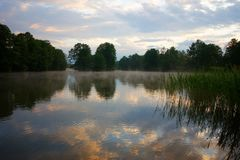 Lake. Durring foggy and cloudy sunrise Royalty Free Stock Photos