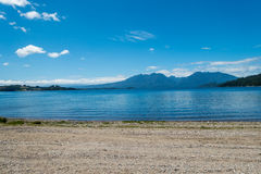 Lake Landscape. Blue tone water and sky in this landscape with a sand road Royalty Free Stock Images