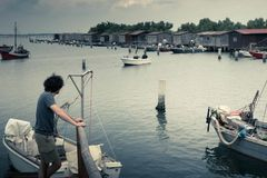 Lake landscape with a boy on a wooden pier watching fishing boats and fishing sheds. Desaturated lake landscape with a boy on a wooden pier watching fishing Stock Photo