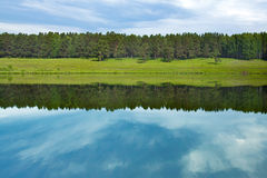 The lake landscape, meadow, forest and sky Stock Photos