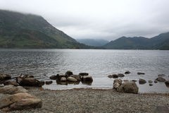Lake landscape in a misty morning. View of a lake with rocks in front of the water, and misty hills behind it in a misty morning Royalty Free Stock Images
