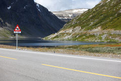 Lake landscape with scenic road and moose sign Royalty Free Stock Image