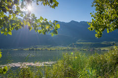 Lake landscape with sun over mountains shining Royalty Free Stock Photos