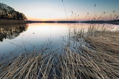 Lake landscape at sunset with bench Stock Photography