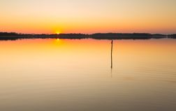 Lake landscape at sunset with bench Stock Photos