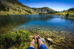 Lake and legs during mountain hiking at Pyrenean mountain Royalty Free Stock Images