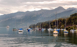 Lake Leman. Pier at Lake Leman in Switzerland, in the background the mountains of the Alps are on a cloudy day Stock Image