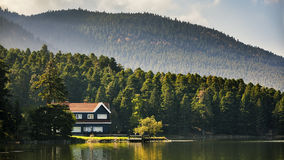 Lake lodge. Image of a lodge on a  lake  surrounded by pine mountains forest taken in the fall season Royalty Free Stock Images