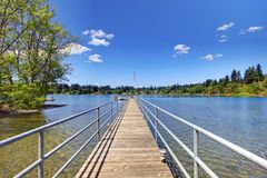Lake with long wood pier and private party raft. Stock Images