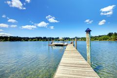 Lake with long wood pier and private party raft. Stock Image