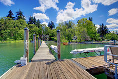 Lake with long wood pier and private party raft. Stock Photos