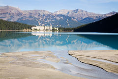 Lake Louise. Blue tinged waters of lake louise reflect the chateau hotel with foreground silt streams that feed the lake and background showing the many snowless Stock Photo