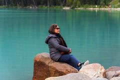 Tourist Poses for a Photo. Lake Louise, Banff, Canada -- August 3, 2018.  A tourist sits on a rock posing for a photo at Lake Louise Stock Photography