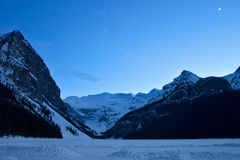 Lake Louise, Banff National Park after dusk. Frozen and snow covered Lake Louise, Alberta, late evening with new moon in the sky Stock Photography