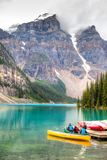 Canoeing on Moraine Lake at Lake Louise in Banff, Canada. LAKE LOUISE, CANADA - AUG 22, 2014: Canoeists prepare their canoe ride on Moraine Lake with clouds Royalty Free Stock Photography