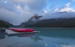 Lake Louise et canoës rouges dans le matin brumeux photographie stock libre de droits