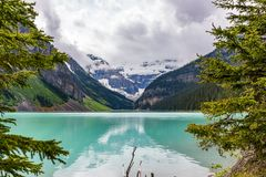Lake Louise framed by trees. With reflection and leading to the mountains and cloudy sky in Canada stock images