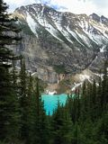 Lake Louise glimpsed through the forest at the base of the Rocki stock images