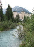 Lake Louise Hotel. An inviting photo of the Lake Louise hotel, backset against the mountains, with a wavy blue stream of water that gently leads the eye to the Stock Photo