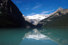 Lake Louise - Jewel of the Rockies. Lake Louise is sometimes referred to as the jewel of the Rockies. At first light a mirror image of Victoria Glacier shimmers Stock Photos
