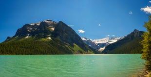 Lake Louise rodeó por los picos y los glaciares de montaña Imágenes de archivo libres de regalías