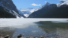 Lake Louise in Springtime, Alberta. Lake Louise, Alberta, with melting lake and rocks in the foreground.  Landscape Stock Image
