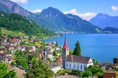 Lake Lucerne and Alps mountains by Weggis, Switzerland. Little swiss town with gothic church on Lake Lucerne and Alps mountain, Switzerland Stock Photo