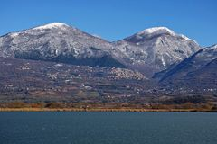 Lake Lungo, Poggio Bustone and massif of Terminillo. Winter, the lake Lungo frozen, the village of Poggio Bustone and part of the massif of Terminillo royalty free stock photos