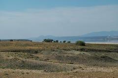 Lake against an arid landscape. Lake Magadi against an arid landscape, Magadi, Rift Valley, Kenya  safari travel scenic beautiful nature natural dry desert stock images