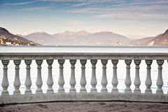 Lake Maggiore landscape. A classical column banister faces the tranquil waters of Lake Maggiore in Italy. On the background the alpine mountain range in a clear Stock Photos