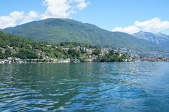 On Lake Maggiore in Switzerland. On Lake Maggiore in Ticino, Switzerland; small towns, houses and forested mountains; in the foreground the lake; blue sky with Stock Image