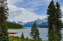 Lake Maligne with red canoes and Rocky Mountains. Beautiful clear Lake Maligne in Banff National Park, Alberta, Canada Royalty Free Stock Photos