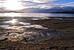 Lake Manapuri sun flare. Sun reflected in pools at edge of Lake Manipuri, NZ royalty free stock images