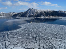 Lake Mashu, Hokkaido. Frozen Lake Mashu with snow capped mountains stock images