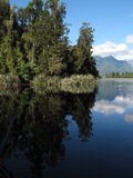 Lake Matheson. Scenic view of trees and mountains reflecting on Lake Matheson, New Zealand royalty free stock photos