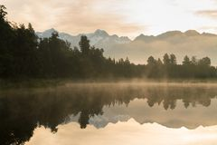 Lake Matheson in early morning with cloudy sky with mount cook. In the background with reflection on the lake, west coast south island New Zealand Stock Image