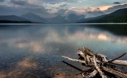 Lake McDonald in Glacier National Park with Sprague Fire in Dist. The Smoke from the Sprague Fire can be seen Across the Still Waters of Lake McDonald in Glacier Royalty Free Stock Images