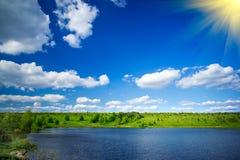 Lake, meadow and blue sky by springtime. Stock Photos