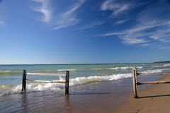 Lake Michigan shore with beach and fences. Waves roll down the beach on the Michigan coast stock images