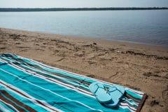 Lake Michigan strand med blåa Flip Flops på handduken Arkivfoton