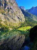 Lake in the middle of the mountains with beautiful reflections in the water. Germany, Bavaria, Obersee - Lake in the middle of the mountains with beautiful royalty free stock photography