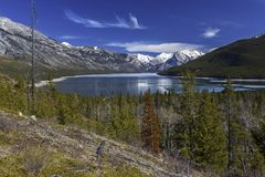 Lake Minnewanka Banff National Park Canadian Rocky Mountains. Distant Panoramic Landscape Scenic View of Lake Minnewanka and Snowy Mountain Tops in Springtime Royalty Free Stock Photography