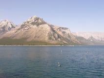 Lake Minnewanka i de steniga bergen i Kanada Fotografering för Bildbyråer