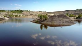 Lake mirror reflects blue sky and trees on island. Amazing panorama lake mirror reflects blue sky with white clouds and small trees growing on island among stock video footage