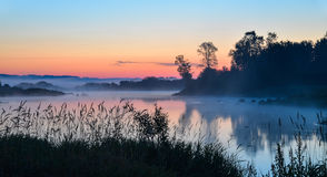Lake in the mist at sunrise, Misty morning landscape Stock Photos