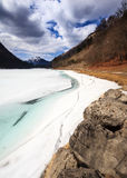 Lake Montriond Thaw. The frozen Lake Montriond beginning to thaw in spring, in the French Alps stock photos